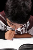 Busy Genius. A genius little kid studying with concentration royalty free stock photos