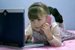 Busy Girl. Young girl playing on laptop and toy phone Stock Photo