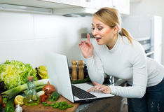 Busy girl cooking with laptop in kitchen Stock Photos
