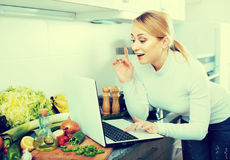 Busy girl cooking with laptop in kitchen Royalty Free Stock Images