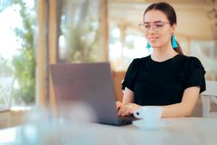 Freelance Woman Working Online Typing on Laptop in a Restaurant. Busy girl using personal computer to work on a remote location royalty free stock images