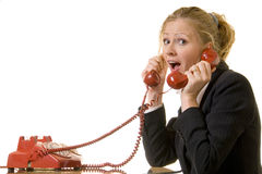 Busy hot line. Blond caucasian woman with two red retro telephone hand sets on ears looking overwhelmed and stressed and busy stock photography