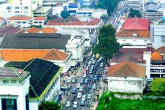 Busy hour in Asia Afrika Street. In Bandung, Indonesia. With many motorcycles and cars in the road, seen from top, tilt shift Royalty Free Stock Photography