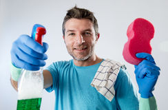 Busy husband smiling happy doing house cleaning with spray bottle and sponge washing glass. Portrait of domestic service man or busy husband smiling happy doing Royalty Free Stock Image