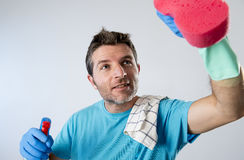 Busy husband smiling happy doing house cleaning with spray bottle and sponge washing glass. Portrait of domestic service man or busy husband smiling happy doing Stock Image