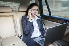 Busy Indian businesswoman working in car Royalty Free Stock Photos