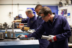 Busy Interior Of Engineering Workshop. With Engineers Wearing Protective Glasses Stock Photography