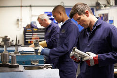 Busy Interior Of Engineering Workshop. With Men Working With Machines Royalty Free Stock Images