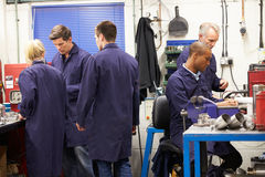 Busy Interior Of Engineering Workshop. With Trainees And Engineers Having Discussions With Each Other Royalty Free Stock Photos