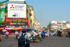 Busy intersection. PHNOM PENH, CAMBODIA - FEBRUARY 27, 2014: A busy intersection in the Cambodian capital has traffic moving in many directions under signs of Royalty Free Stock Photos