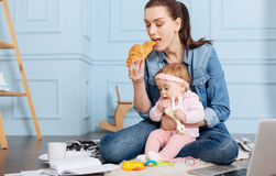 Busy inventive mom eating brunch with her daughter. Making two things at once. Joyful energetic young mother spending Sunday morning with her family while Stock Images
