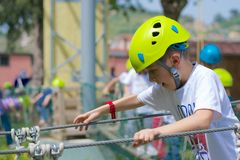 Busy kid at ropes course. With helmet Royalty Free Stock Photography