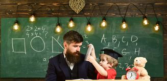 Busy kid studying at school. Father checking homework, helps to boy, son. Individual studying concept. Teacher in formal stock photography
