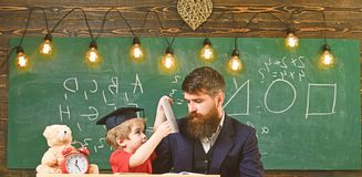 Busy kid studying at school. Father checking homework, helps to boy, son. Individual studying concept. Teacher in formal. Wear and pupil in mortarboard in royalty free stock photo