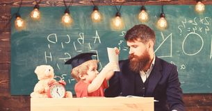 Busy kid studying at school. Teacher, father checking homework, helps to boy, son. Individual studying concept. Teacher royalty free stock photos