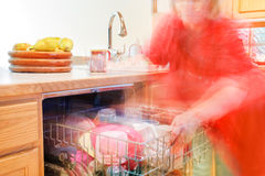 Busy in the kitchen. Woman busily moving about - getting things out of the dishwasher royalty free stock photo