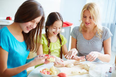 Busy at the kitchen. Two girls preparing food with their mother stock photo