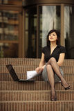 Busy lady with sexy legs. Busy business lady with sexy legs outdoors with laptop in front of an office building on the stairs in the city Royalty Free Stock Photo