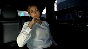 Busy lady sitting in car, planning future, personal assistant waiting outside. Stock photo stock photography