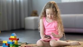 Busy little girl using mobile gadget, playing games on smartphone, technology
