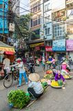 Busy local daily life of the morning street market in Hanoi, Vietnam. A busy crowd of sellers and buyers in the market. Stock Photos