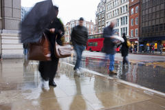 Busy london commuters in the pouring rain. With umbrellas and coats Stock Photography