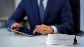 Busy male cost estimator using tablet pc, planning product manufacture project stock photography