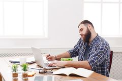 Busy male programmer has business lunch in modern office interior Royalty Free Stock Images