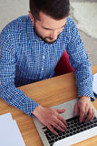 Busy male working in laptop while sitting in red armchair. High-angled shot of busy male working in laptop while sitting in red armchair Royalty Free Stock Image