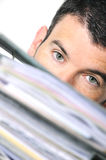 Busy man. Hiding behind a stack of files Royalty Free Stock Photography