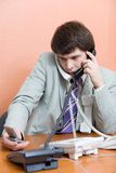 Busy man. A young man talking on the phones at office Stock Photo