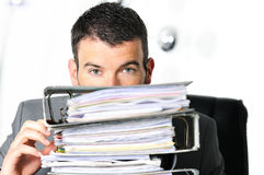 Busy man. Hiding behind a stack of files Stock Image