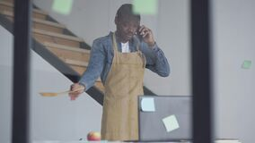 Busy man in apron talking on the phone gesturing with cooking shovel. Portrait of confident African American employee