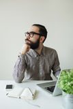 Busy man with beard in glasses thinking over laptop and smartpho Royalty Free Stock Photography