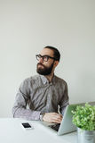 Busy man with beard in glasses thinking over laptop and smartpho Stock Photo