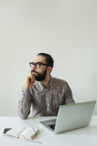 Busy man with beard in glasses thinking over laptop and smartpho Stock Images
