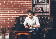Busy man calls a phone number. Businessman is in his cabinet behind his laptop on the background of wall with decorative bricks stock images