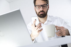 Busy man with a cell phone and a coffee cup Royalty Free Stock Images