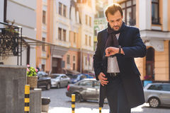Busy man checking time while walking Royalty Free Stock Photos