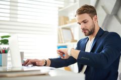 Busy man checking time at work stock image