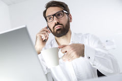 Busy man with coffee on his phone Stock Image