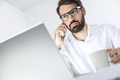Busy man with coffee and laptop on phone Royalty Free Stock Photos