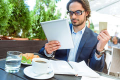 Busy man deals with business while paying bill Stock Photo