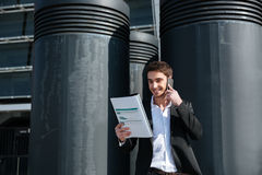 Busy man holding documents and talking on phone. Young busy man talking on phone about documents in the street Stock Photography