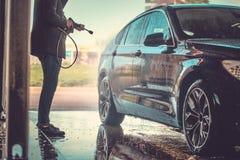 Busy man is washing his own car at car washing station. royalty free stock photos