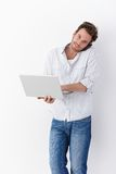 Busy man with mobile and laptop smiling Stock Photo