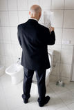 Busy man reading news in loo Royalty Free Stock Photos