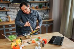 Busy man stand at table in kitchen and blend eggs. He talk on phone and look down. Colorful vegetables lying on desk. Busy man stand at table in kitchen and royalty free stock photography