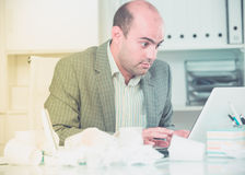 Busy man in suit worrying at the computer Royalty Free Stock Image