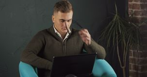 Busy man uses laptop. Busy, focused man thinking on the task while typing on black laptop, sitting in comfortable, aqua green armchair, indoor shoot in big and stock video footage